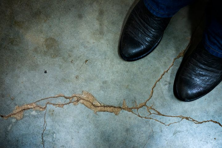 Gary Landra stands on a crack across his basement floor that he says was caused by an earthquake in Prague, Oklahoma. A