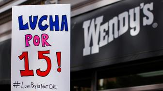 """A protester holds up a placard during a gathering outside a Wendy's fast food restaurant in support of a nation-wide strike and protest to raise the hourly minimum wage of fast food workers to $15 in San Diego, California December 5, 2013. Fast-food workers in hundreds of U.S. cities staged a day of strikes and rallies on Thursday to demand higher wages, saying the pay was too low to feed a family and forced most to accept public assistance. The sign reads, """"Fight for 15"""".  REUTERS/Mike Blake  (UNITED STATES - Tags: FOOD BUSINESS CIVIL UNREST EMPLOYMENT)"""