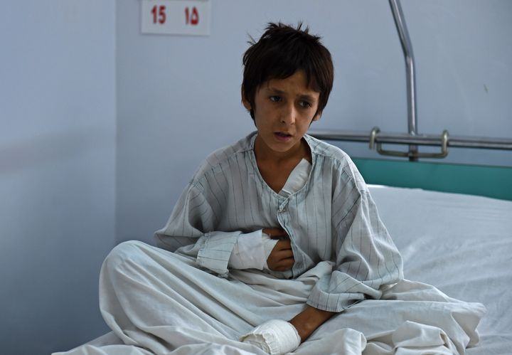 A wounded Afghan boy who survived U.S. airstrikes on the MSF Hospital in Kunduz sits on his bed at the Italian-run