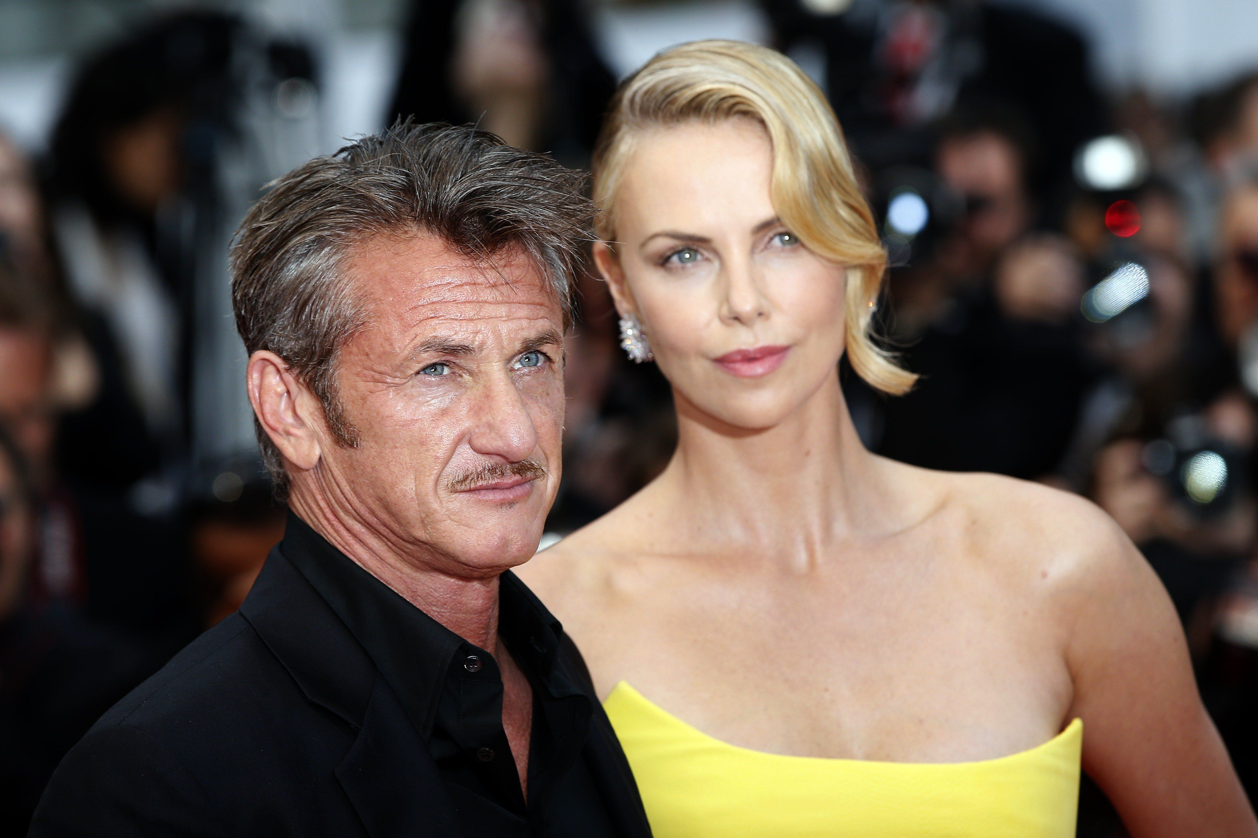 US actor Sean Penn (L) and his partner South African-US actress Charlize Theron pose as they arrive for the screening of the film 'Mad Max : Fury Road' during the 68th Cannes Film Festival in Cannes, southeastern France, on May 14, 2015.   AFP PHOTO / VALERY HACHE        (Photo credit should read VALERY HACHE/AFP/Getty Images)