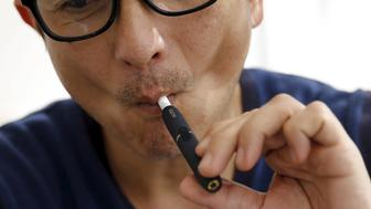 "A customer tries a Philip Morris' ""iQOS"" smokeless tobacco e-cigarette at an iQOS store in Tokyo, Japan, March 3, 2016.   REUTERS/Toru Hanai"