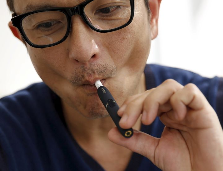 "A customer tries a Philip Morris' ""iQOS"" smokeless tobacco e-cigarette at an iQOS store in Tokyo, Japan, March 3, 2016."