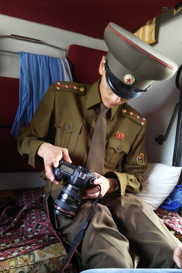 A customs officer checks a passenger's cameraon a train from Moscow to Pyongyang at the Tumangang railway station.