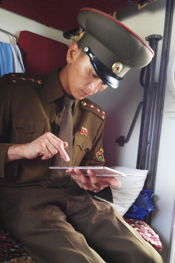 A customs officer checks a passenger's mobile device.