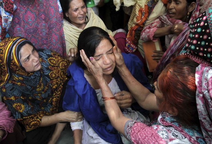 Family members comfort a woman mourns the death of a relative, who was killed in a blast outside a public park on Sunday, dur