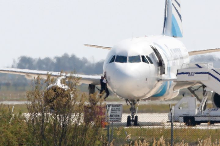 A man tries to leave the plane by climbing out of the cockpit. Conflicting theories emerged about the Egyptian hijacker's mot
