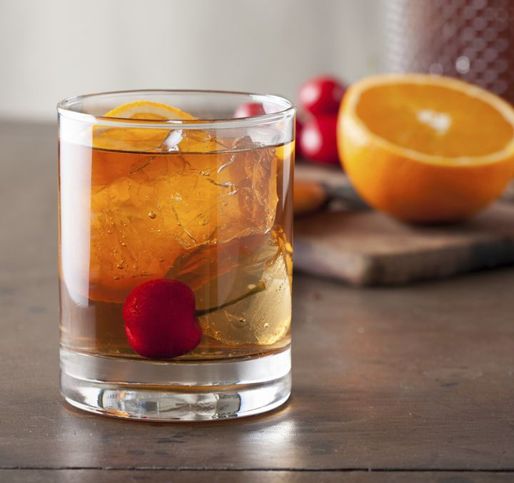A classic old-fashioned cocktail with a cherry on a wooden table.