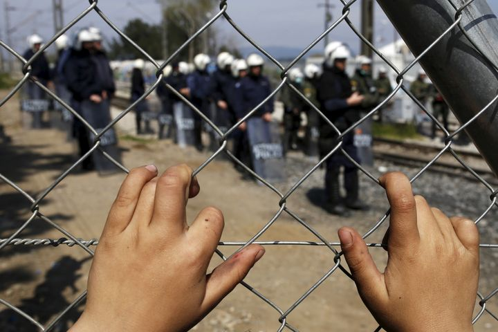 A child places his hands on a fence as Greek police officers stand guard after minor clashes occurred at a makeshift camp for