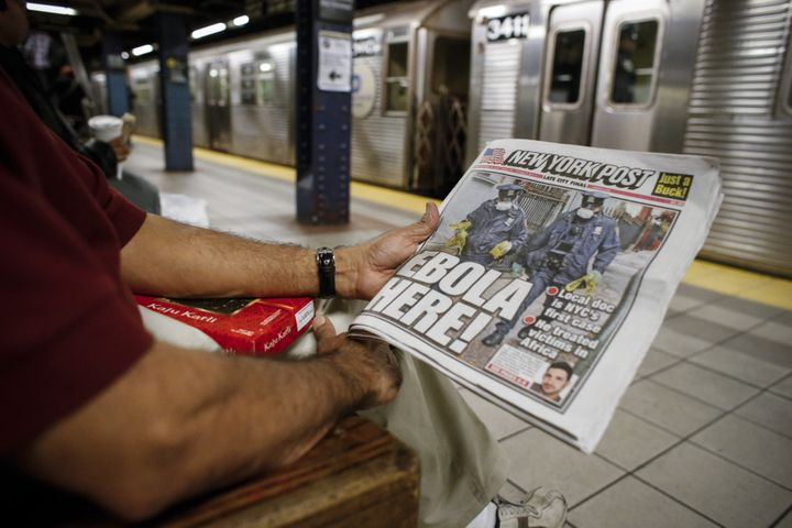 A man shows the front page of a local newspaper while reading in the New York City subway on Oct. 24, 2014. The headline refe