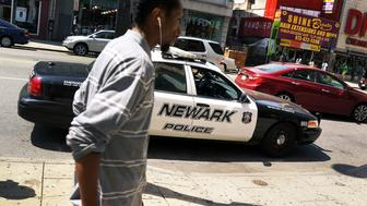 NEWARK, NJ - MAY 13:  A man walks by a police car in downtown on May 13, 2014 in Newark, New Jersey. Voters in New Jersey's largest city go to the polls on May 13, to choose a new mayor following Democrat Cory Booker's departure to the U.S. Senate. Newark, which is approximately 12 miles from New York City, is struggling with a rise in violent crime and unemployment. Shavar Jeffries, 39, and Ras Baraka, 44, are the two democrats running for the job in the heavily Democratic city.  (Photo by Spencer Platt/Getty Images)