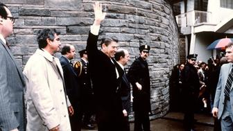 This photo taken by presidential photographer Mike Evens on March 30, 1981 shows President Ronald Reagan waving to the crowd just before the assassination attempt on him, after a conference outside the Hilton Hotel in Washington, D.C.. Reagan was hit by one of six shots fired by John Hinckley, who also seriously injured press secretary James Brady (just behind the car).  Reagan was hit in the chest and was hospitalized for 12 days. Hinckley was aquitted 21 June 1982 after a jury found him mentally unstable. (Photo credit should read MIKE EVENS/AFP/Getty Images)