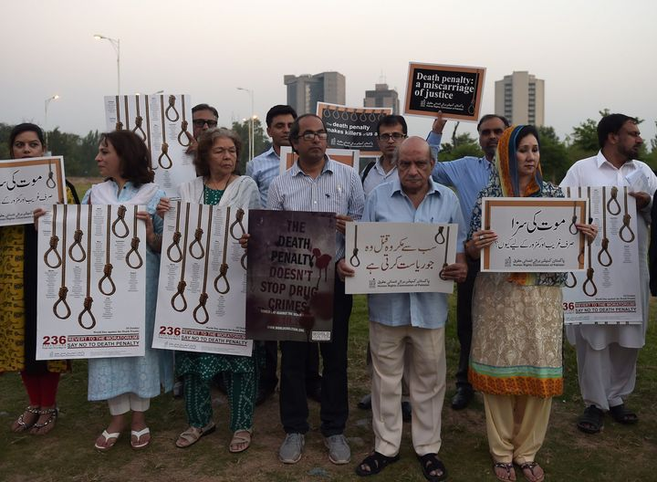 Activists from the Human Rights Commission of Pakistan carry placards during a demonstration to mark International Day Agains