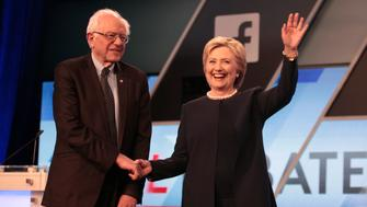 Democratic U.S. presidential candidates Senator Bernie Sanders and Hillary Clinton shake hands before the start of the Univision News and Washington Post Democratic U.S. presidential candidates debate in Kendall, Florida March 9, 2016.    REUTERS/Javier Galeano
