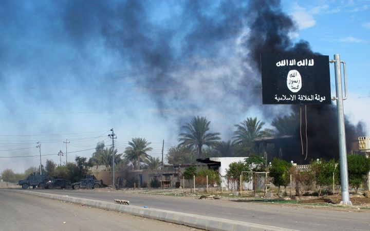 Smoke rises behind an Islamic State flag in Saadiya, Iraq.