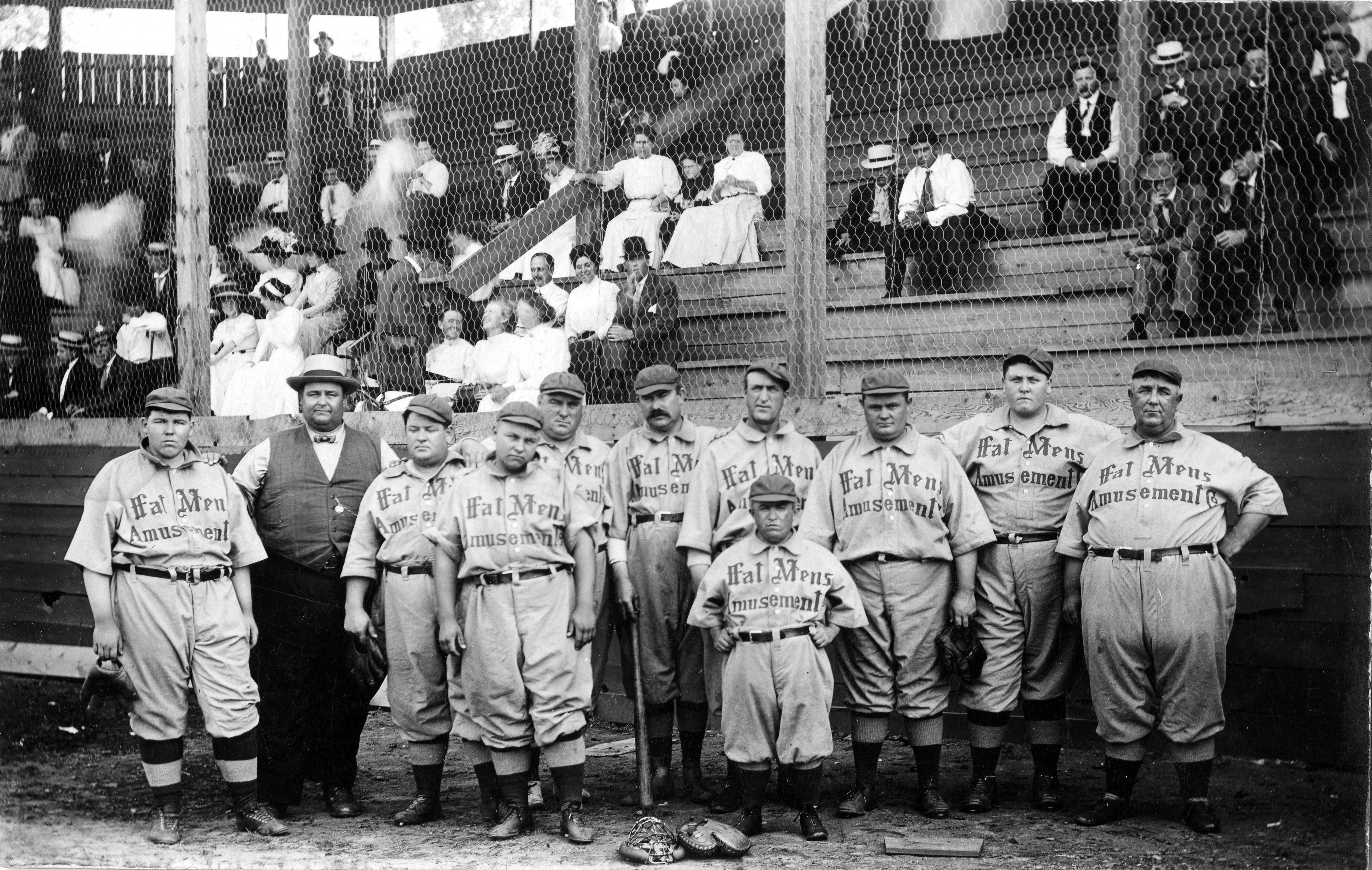 "Players on The Fat Man's Baseball Association, wear jerseys written with ""Fat Mens Amusement"" across it and pose in their home ballpark (unknown location) in 1910."