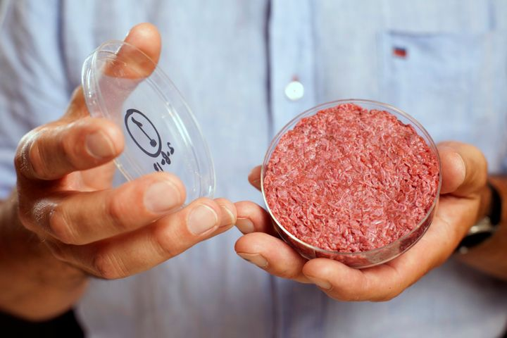 Professor Mark Post holds the world's first lab-grown beef burger during a launch event on Aug. 5, 2013. Post is just one of