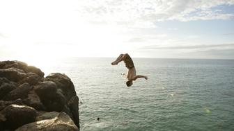 View of a man diving into the sea from cliff
