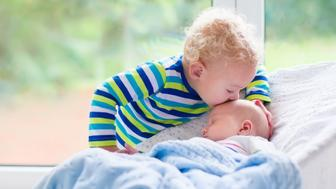 Cute little boy kissing his newborn brother. Toddler kid meeting new born sibling. Infant sleeping in white bouncer under a blanket. Kids playing and bonding. Children with small age difference.