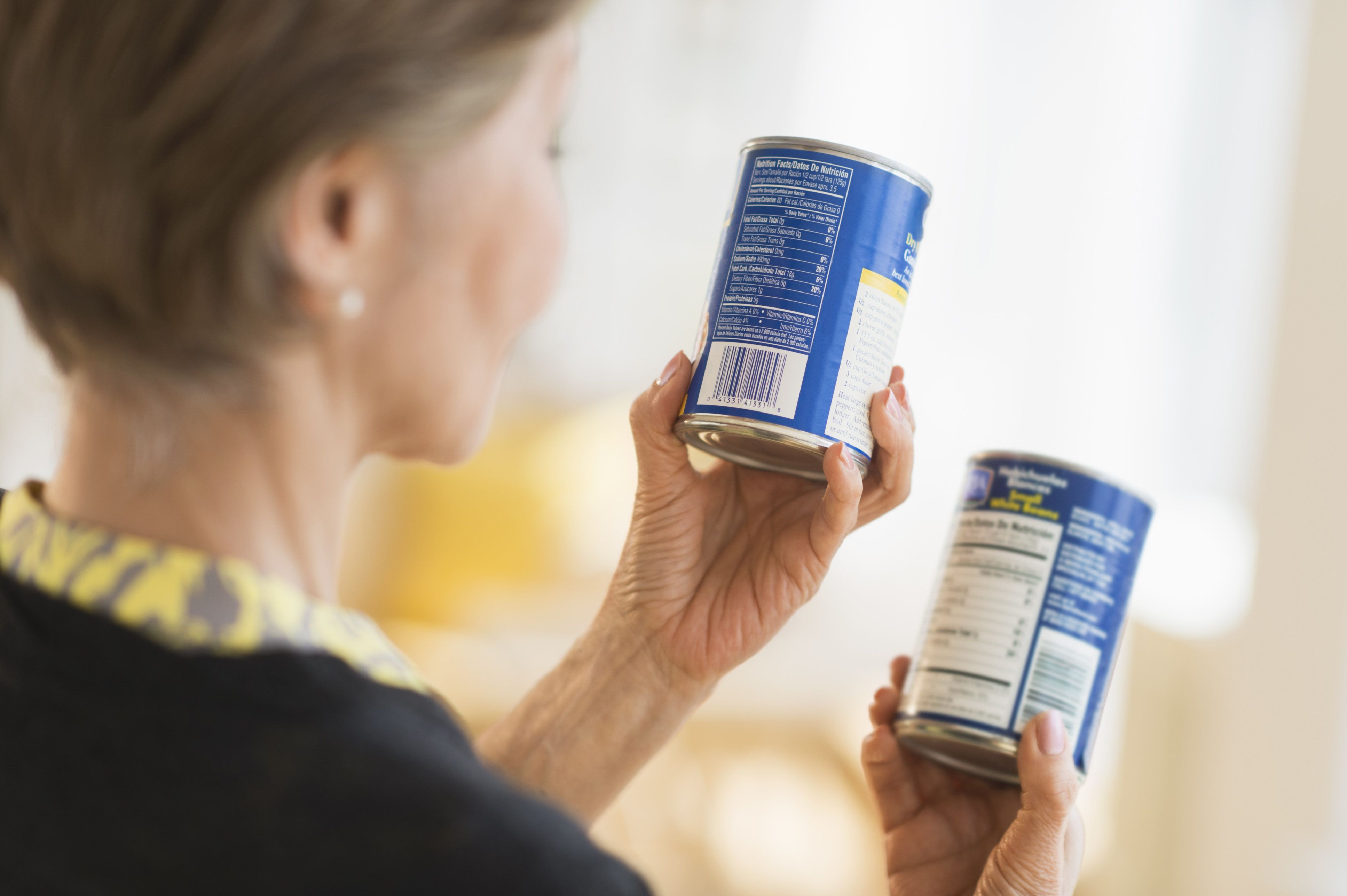 USA, New Jersey, Jersey City, Senior woman reading labels on canned food