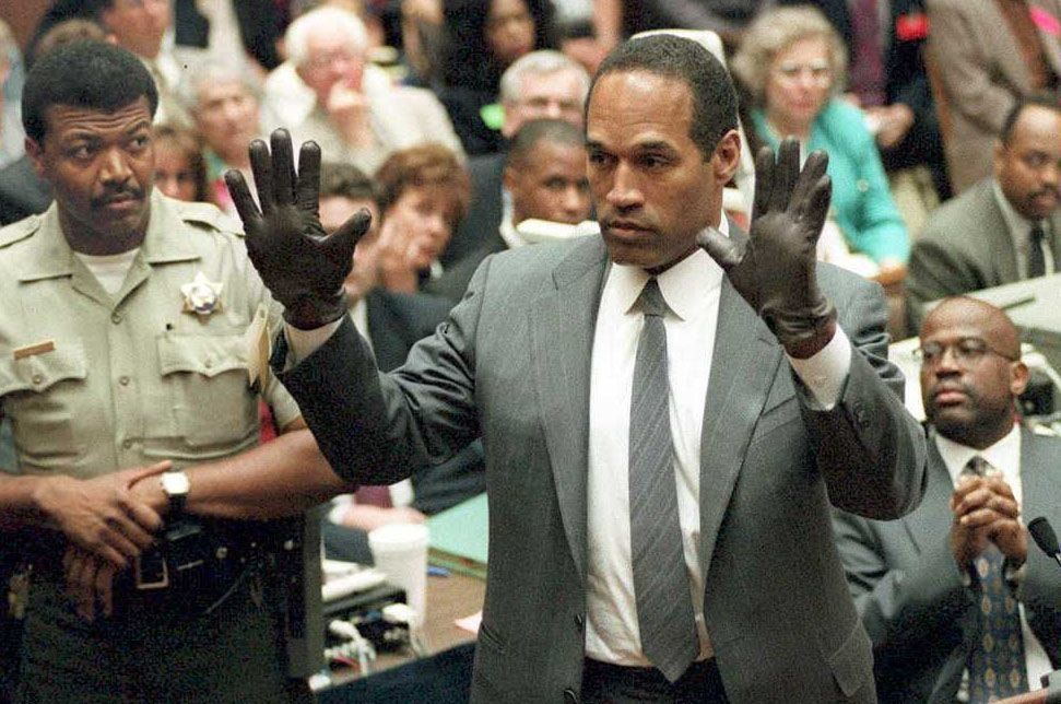 LOS ANGELES, CA - JUNE 21:  O.J. Simpson shows the jury a new pair of Aris extra-large gloves, similar to the gloves found at the Bundy and Rockingham crime scene 21 June 1995, during his double murder trial in Los Angeles,CA. Deputy Sheriff Roland Jex(L) and Prosecutor Christopher Darden (R) look on.  (Photo credit should read VINCE BUCCI/AFP/Getty Images)