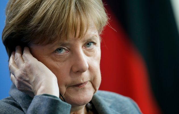 German Chancellor Angela Merkel adjusts her earphones as she addresses a news conference following her...
