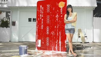 Young chinese american woman stands next to oversized credit card in driveway covered with bubbles in the process of being washed.  The card is a life-sized prop designed and created by the photographer.  The image is not a composite.