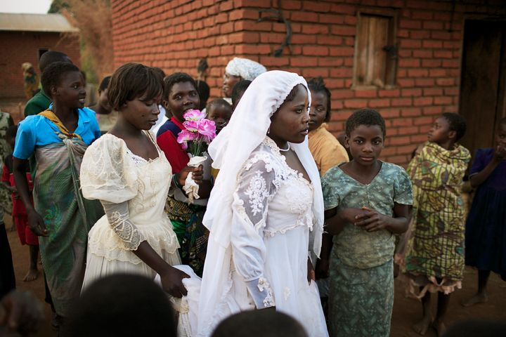 Suzana Nabanda, age 16, walks with her sister after a marriage ceremony in 2006, in a poor village in Malawi. She just g