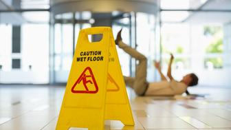 Businessman slipping on wet office floor