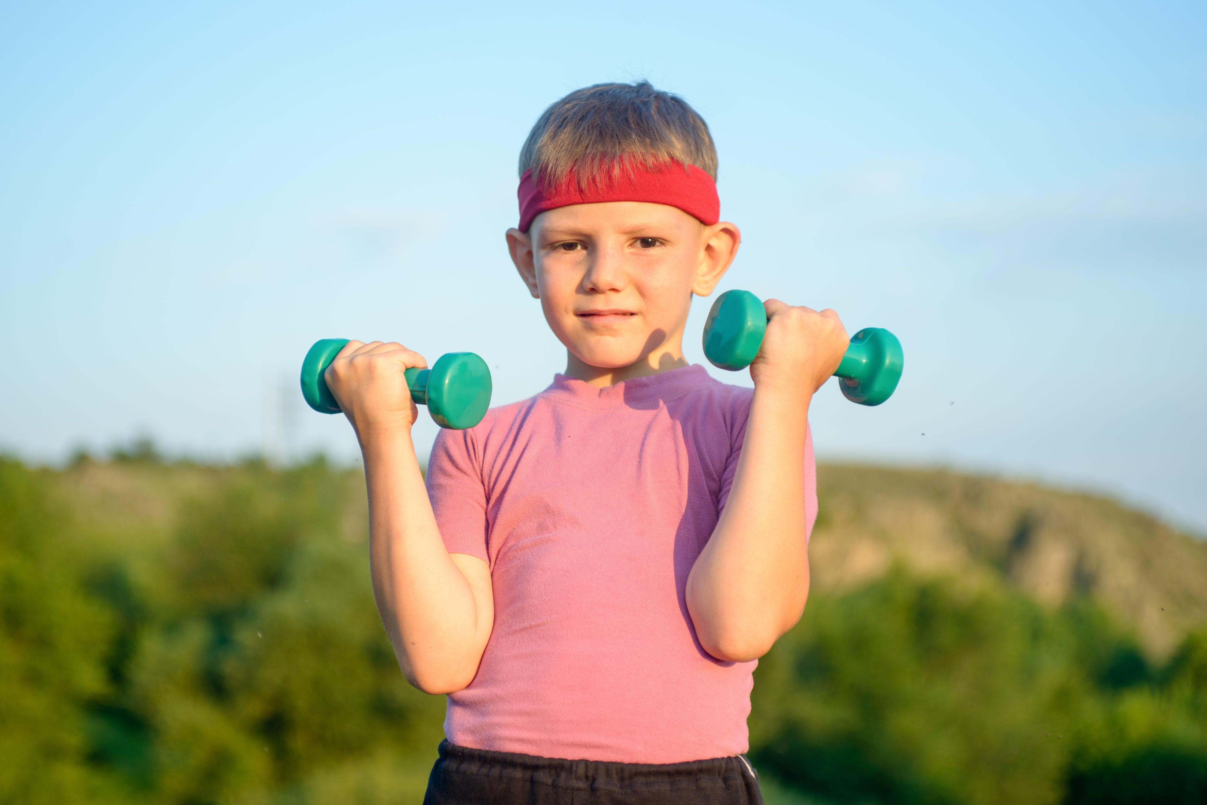 Half Body Shot of an Athletic Cute Boy with Red Warrior Headband, Lifting Two Small Dumbbells and Looking at the Camera Against Green Mountain and Sky.