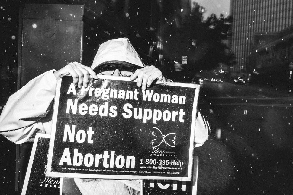 Sept. 29, 2015 - Protester hides face behind protest sign outside of Planned Parenthood on Liberty Avenue in Pittsburgh, PA.