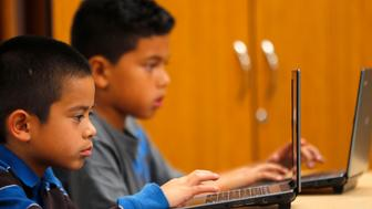 Grade four students work on laptop computers at Monarch School in San Diego, California October 8, 2013. While most of San Diego County is wired for broadband access, the Public Policy Institute of California reports 23 percent of local residents have not connected to a service. Students are going home with digital assignments, or with school-issued technology, but with no active broadband connection in the home, according to a media release.      REUTERS/Mike Blake  (UNITED STATES - Tags: EDUCATION SCIENCE TECHNOLOGY POLITICS BUSINESS TELECOMS)