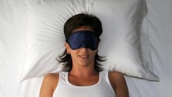 Beautiful sleeping young woman in sleep eye mask.