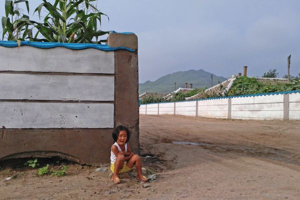 A child rests in the village.