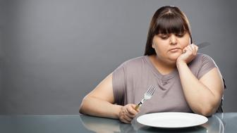 Overweight woman looking at empty plate in front of her, studio shot