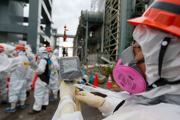 A Tokyo Electric Power Co. employee measures radiation levels as workers conduct operations to construct...