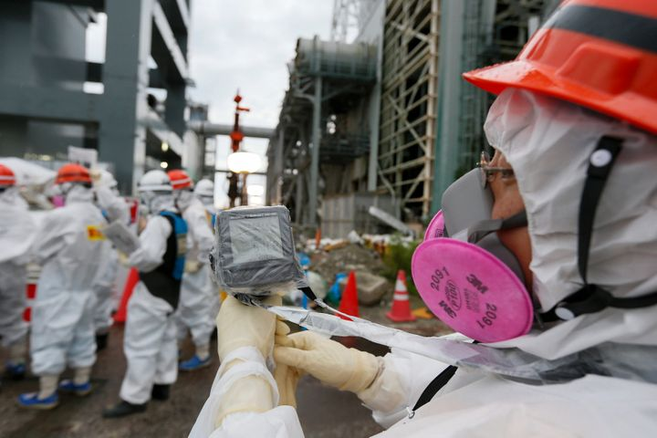 A Tokyo Electric Power Co. employee measures radiation levels as workers conduct operations to construct an underground ice w