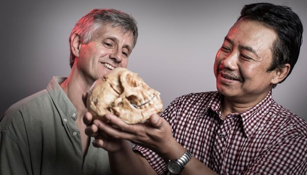 The University of Wollongong's Dr. Richard Roberts and Dr. Thomas Sutikna, holding a copy of a Homo...