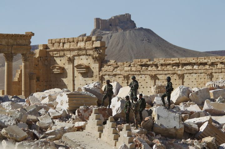 Syrian army soldiers stands on the ruins of the Temple of Bel in the historic city of Palmyra. Syria said some 40 bodies were