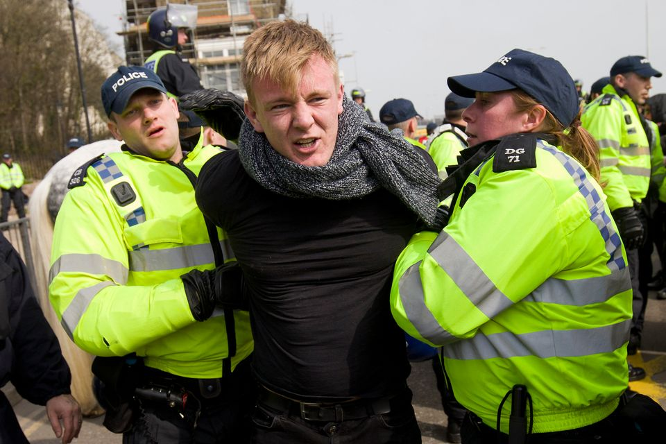 A man is led away by police as anti-racism demonstrators block the route of a planned far right march...