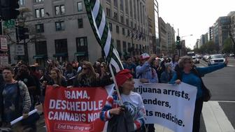 Protesters march down Washington, DC's K Street on April 2, 2016, after smoking marijuana in front of the White House.