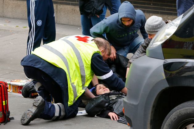 A Muslim woman is attended to by paramedics after being struck by a car that ploughed through a police