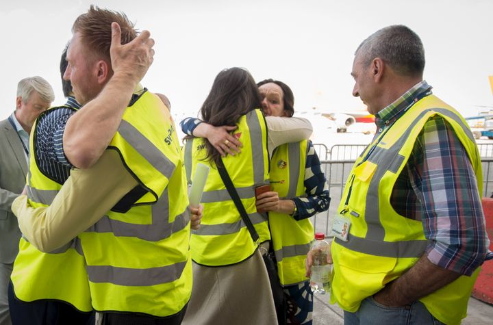 Brussels Airport staff hug as the first plane takes off from Brussels Airport, which partially re-opened following a bomb bla