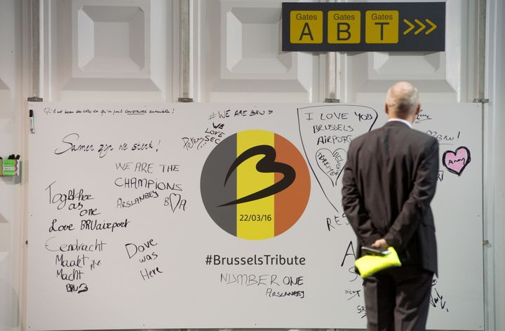 A man looks at a tribute board at Brussels Airport, which partially re-open following a bomb blast 12 days ago, in Zaventem,