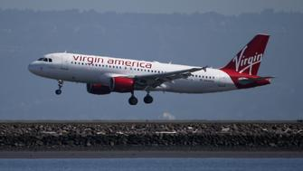 BURLINGAME, CA - MARCH 29:  A Virgin America plane lands at San Francisco International Airport on March 29, 2016 in Burlingame, California. JetBlue Airways and Alaska Air Group are reportedly preparing takeover offer bids for Virgin America airlines.  (Photo by Justin Sullivan/Getty Images)