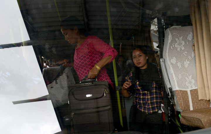 Nepalese women, rescued from a suspected trafficking scheme in India, board a bus on their arrival at Kathmandu's internation