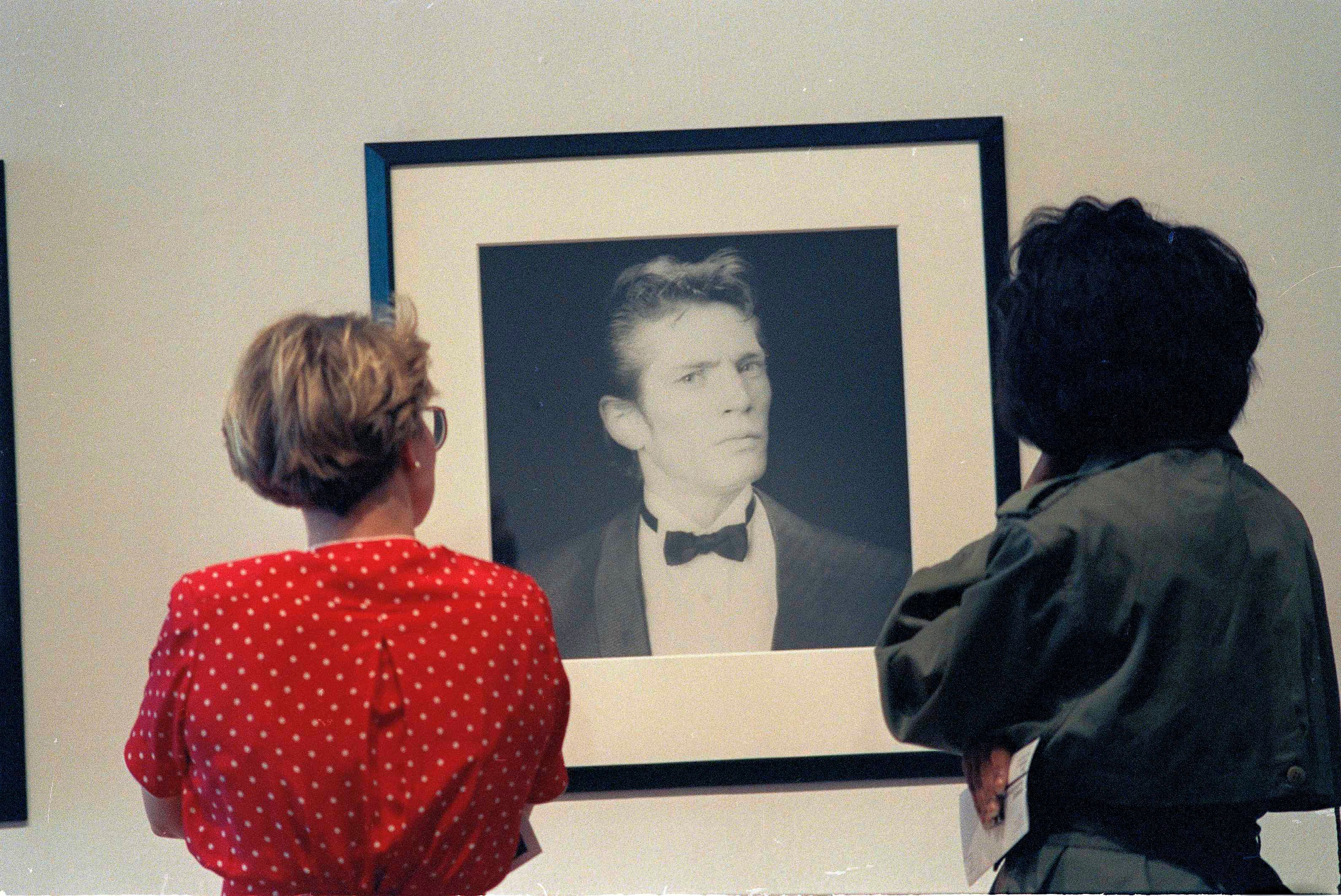 Two women look at a self-portrait of photographer Robert Mapplethorpe done in 1986 while viewing the exhibit at the Contemporary Arts Center in Cincinnati, Ohio, April 9, 1990. (AP Photo/Al Behrman)