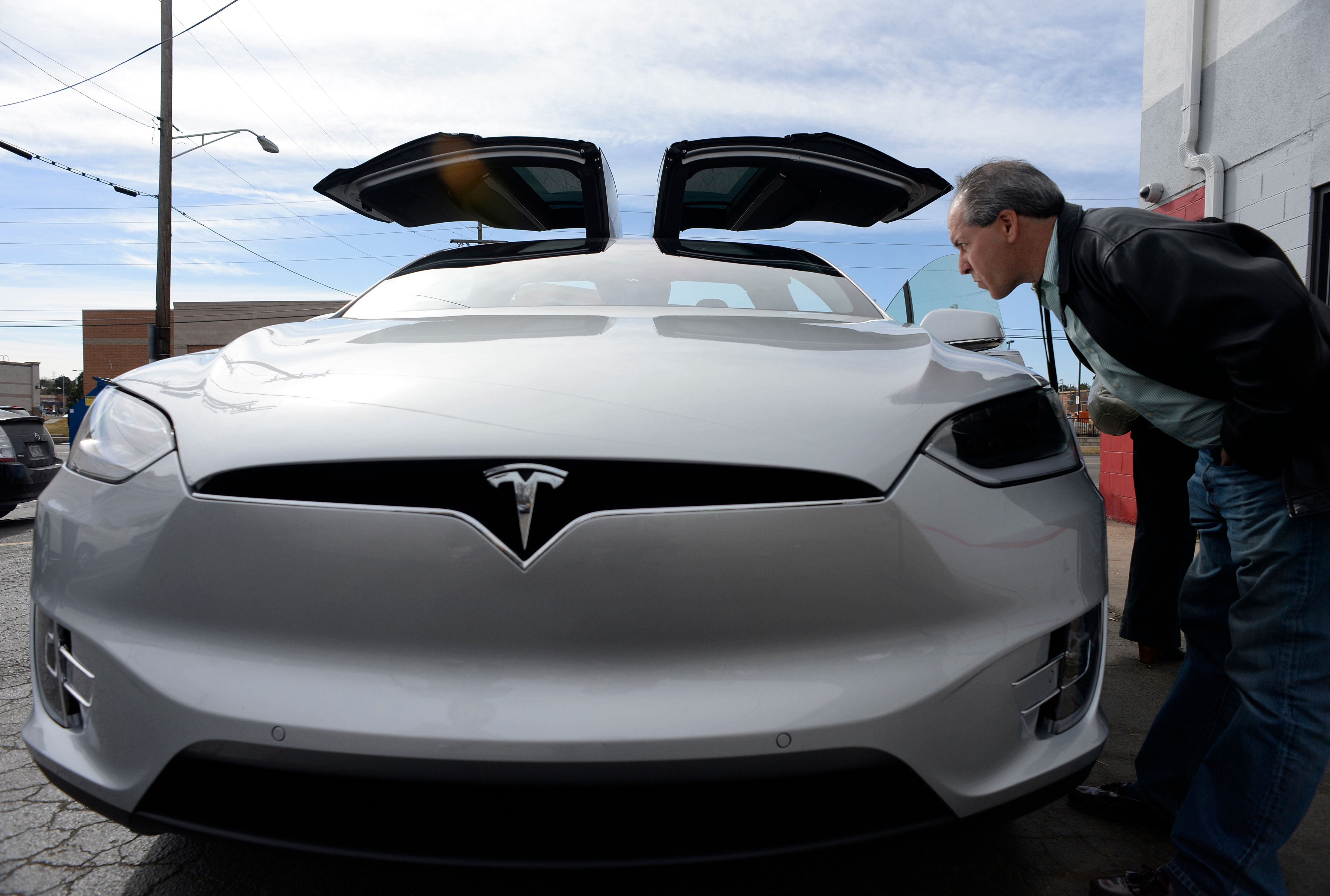 DENVER, CO - March 04: Jonathan Sollender looks over the finish on the new Tesla Model X P90D on display at Tesla Motors March 04, 2016. The Tesla Model X P90D electric vehicle travels 0-60 in 3.8 seconds, has Falcon Wings for passenger doors, seats 7 passengers and has a 250-mile range per charge. Customers who pre-ordered the car got a firsthand look and a test drive Friday. (Photo by Andy Cross/The Denver Post via Getty Images)