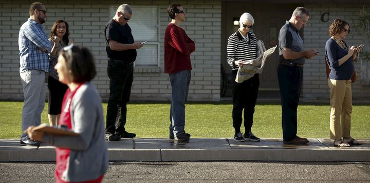 People wait to vote in the U.S. presidential primary outside a polling site in Glendale, Arizona, on March 22, 2016. The Depa