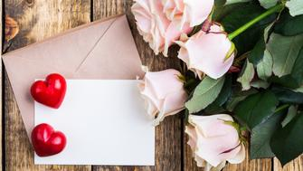 Pink roses and two red hearts on a rustic wooden board. Envelope and empty blank card for message on Valentine's Day. Valentine's Day background, top view