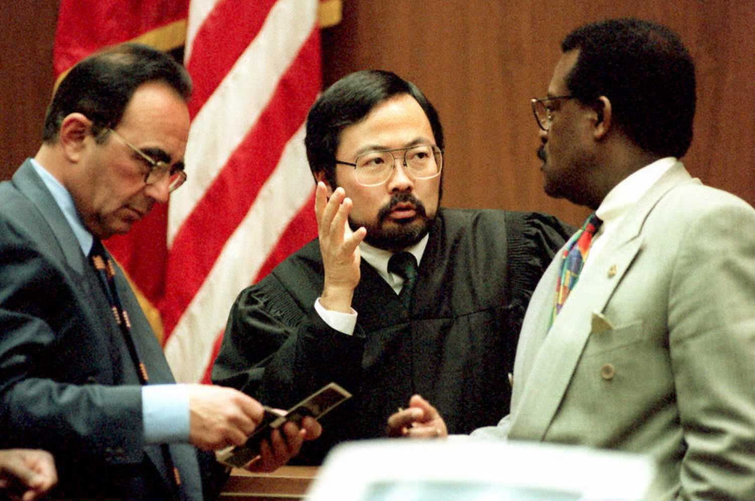 LOS ANGELES, CA - JANUARY 31:  O.J. Simpson defense attorneys Robert Shapiro (L) and Johnnie Cochran Jr. (R) meet Judge Lance Ito (C) 31 January during a sidebar in Simpson's double murder trial.  Shapiro is looking at Polaroids taken of Simpson's ex-wife Nichole Brown-Simpson after a beating incident on 01 January  1989.   (COLOR KEY: Red in flag). AFP PHOTO  (Photo credit should read POO/AFP/Getty Images)